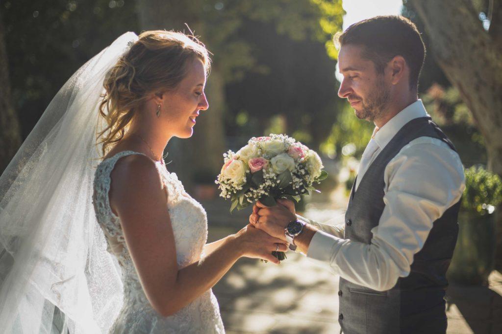 Séance couple, les mariés face à face tenant le bouquet de la mariée