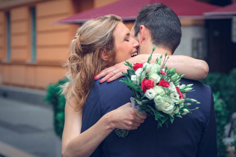 Câlin des mariés avant leur cérémonie civil avec le beau bouquet de la mariée en premier plan.