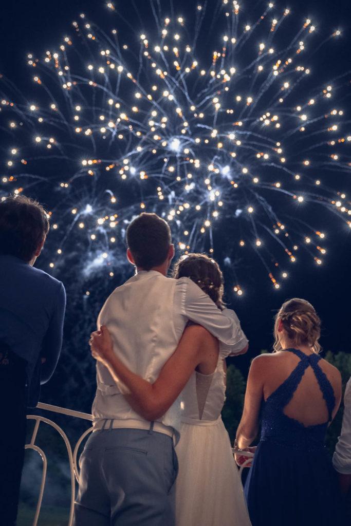 Les mariés de dos contemplant un feux d'artifice tiré en leur honneur pour leur mariage
