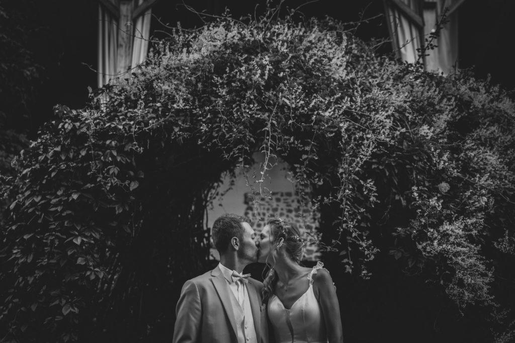 Les mariés s'embrassent devant une grande arche fleurie pour leur séance couple
