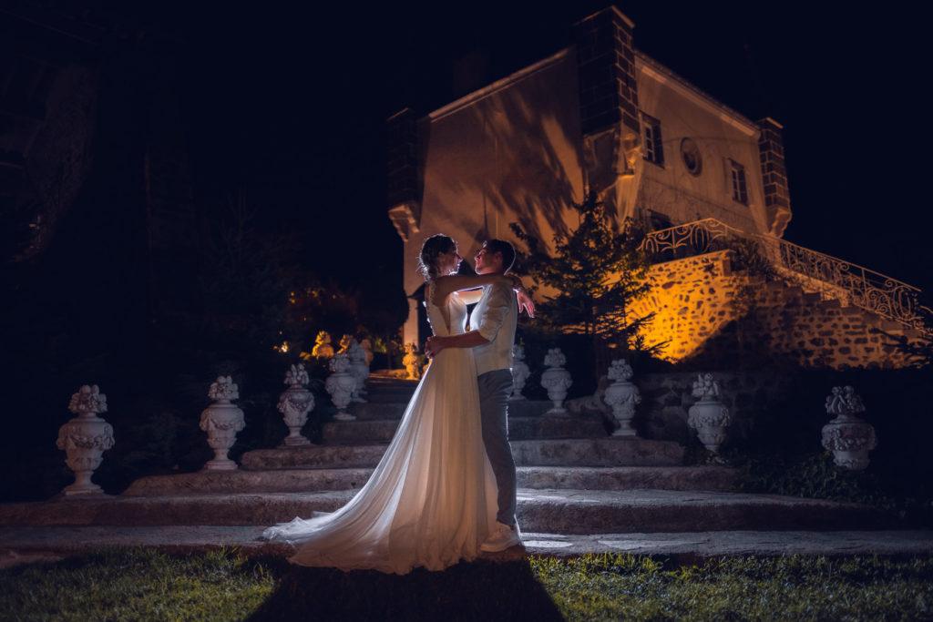 Les mariés se regardent face à face de nuit devant un château, la robe de mariée et bien mise en valeur