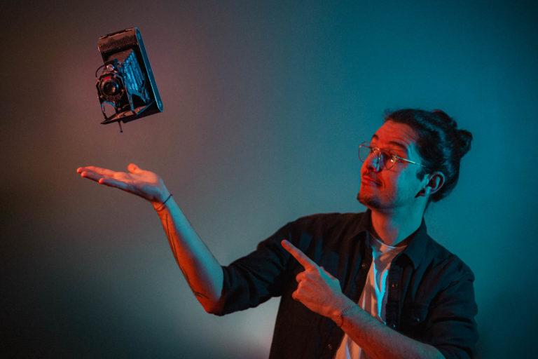 Le photographe de mariage Aurélien Kirchner sur un fond coloré bleu en train de lancer un appareil photo ancien.