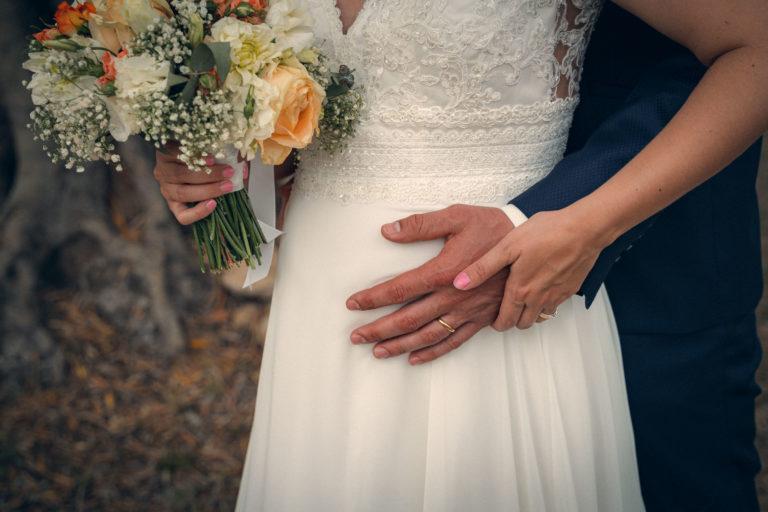 Les mains des mariés qui se rencontre sur le ventre de madame, on voit leurs alliances, la mariée tiens son bouquet dans son autre main.
