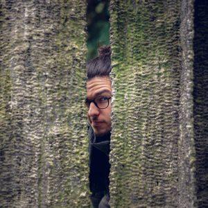 Portrait du photographe de mariage Aurélien Kirchner, caché entre deux arbres.