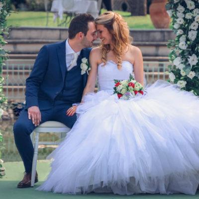 Les mariés assis, front contre front pendant leur cérémonie laïque, ils sont devant leur arche fleurie.
