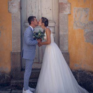 Mariés qui s'embrassent devant une jolie porte d'époque dans la ville pour leur séance couple le jour de leur mariage.